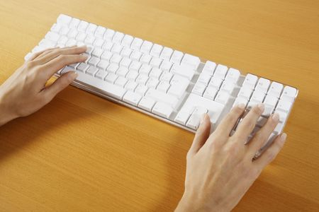 hand typing on a wireless white keyboard computer posed on atable