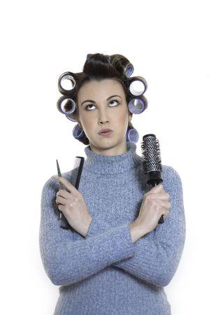 Studioaufnahme Porträts einer jungen lustigen und süßen Frau auf weißem Hintergrund, die ein Lockenwickler-Opfer ist