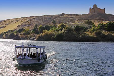 Barco de crucero por el río Nilo con la tumba de Aga Khan en la orilla cerca de Asuán en Egipto