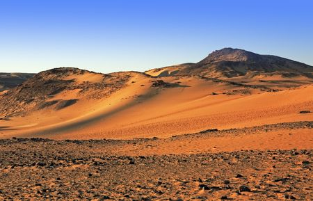 desert sand dune at sunset with blue sky