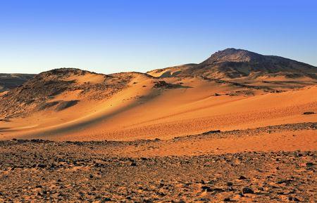 Duna de arena del desierto al atardecer con cielo azul