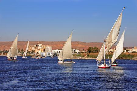 Faluchos navegando por el río Nilo cerca de Asuán en Egipto Foto de archivo