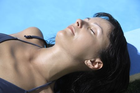 young beautiful caucasian brunette woman relaxing or sleeping near a swimming pool geting tanned by the sun Фото со стока
