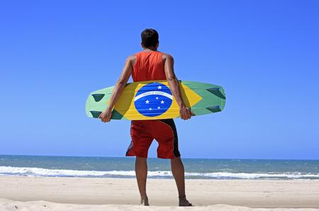 Kite surfer con la bandiera brasiliana dipinta sulla tavola con