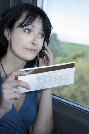 beautiful young woman  in a train making a phone call  with a ticket in his hand Stock Photo