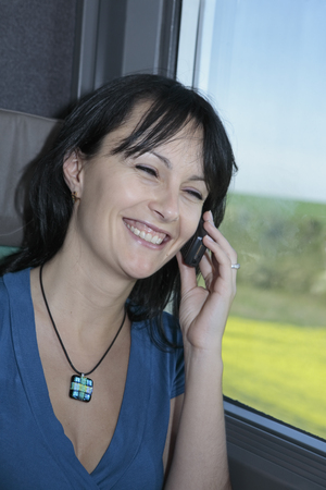 beautiful young woman  in a train smiling and making a phone call