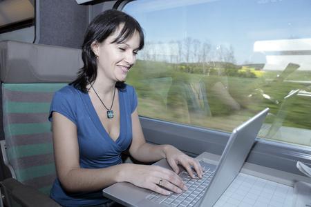 beautiful young woman woman in a train using a computer lap top Banco de Imagens