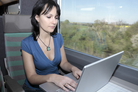beautiful young woman woman in a train using a computer lap top Imagens