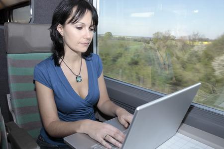 Hermosa mujer joven en un tren usando una computadora portátil