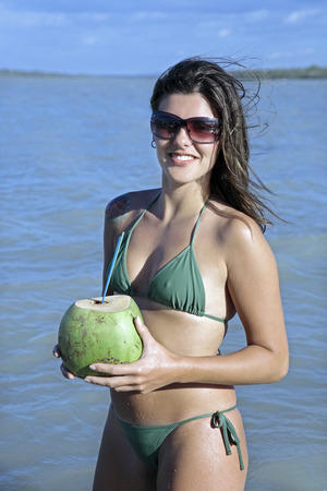 beautiful smiling bikini dressed young brazilian  woman drinking and holding fresh coconut juice in the tatajuba lagoon in jericoacoara ceara state near fortaleza