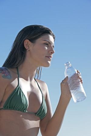 beautiful smiling bikini dressed young brazilian  woman in jericoacoara ceara state near fortaleza driking water Stock Photo