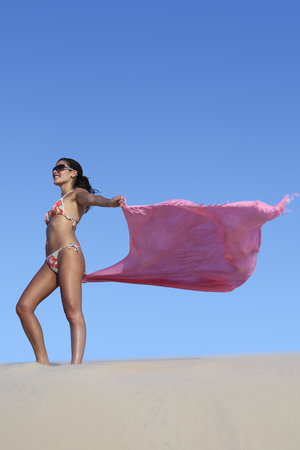 beautiful smiling bikini dressed young brazilian  woman in the wind of the sand dune of jericoacoara ceara state near fortaleza floating his sarong