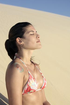 beautiful smiling bikini dressed young brazilian  woman medtating on the sand dune of  jericoacoara ceara state near fortaleza Stock Photo