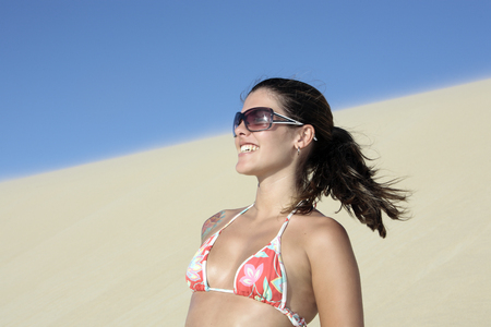 beautiful smiling bikini dressed young brazilian  woman in the wind of the sand dune of jericoacoara ceara state near fortaleza looking at the sun Фото со стока