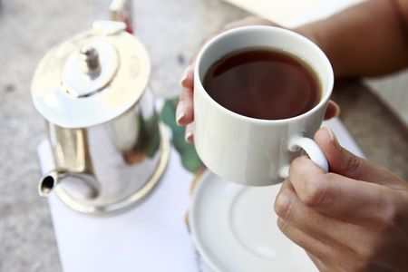 close up of hands serving tea in a cup from a teacup