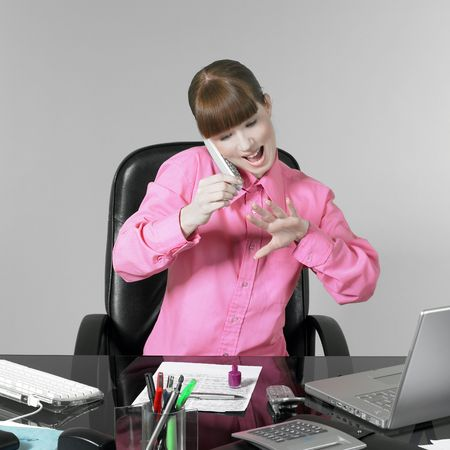 young woman at the office desk multi-tasking
