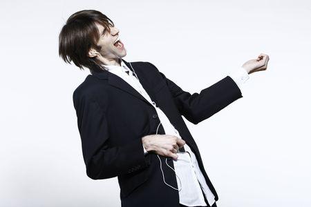 Studioaufnahme Porträt eines jungen lustigen, ausdrucksstarken, dünnen und großen Mannes auf isoliertem Hintergrund, der einem MP3-Player Musik hört, der ein Luftgitarrenheld ist, der vortäuscht zu spielen Standard-Bild