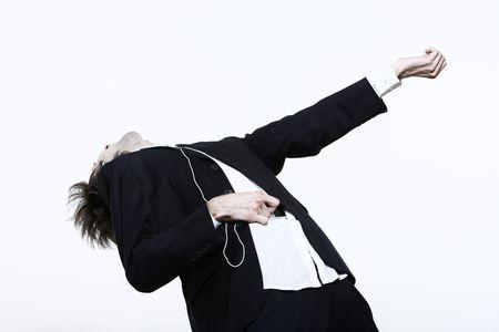 Studioaufnahme Porträt eines jungen lustigen, ausdrucksstarken, dünnen und großen Mannes auf isoliertem Hintergrund, der einem MP3-Player Musik hört, der ein Luftgitarrenheld ist, der vortäuscht zu spielen