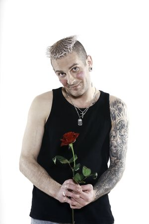 studio shot  blushing heart shy man  with tatoos and piercing holding a rose