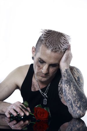 studio shot of a sad   man  with tatoos and piercing 写真素材
