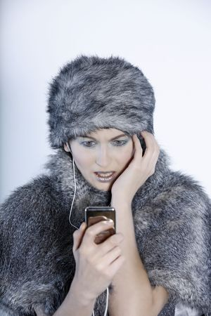 studio shot portrait of a beautiful woman russian type in a fur coat and hat studio shot portrait of a beautiful woman russian type in a fur coat and hat using her multimedia player watching video
