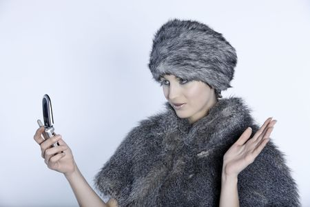 studio shot portrait of a beautiful woman russian type in a fur coat and hat and saying hello by cellphone