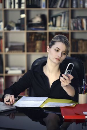 businesswoman at the office desk using her phone
