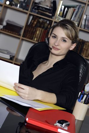 smiling businesswoman at the office desk with microphone headset