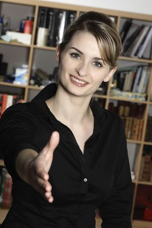 sonriente, mujer de negocios, en la oficina, extensión, un, apretón de manos Foto de archivo