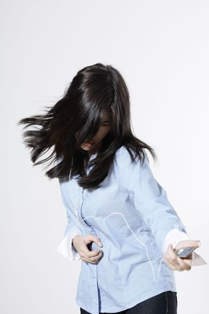 studio shot isolated portrait of a young cute asian woman listening to mp3 player