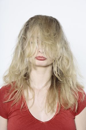 studio shot portrait isolated of young blond long hair woman in hairstyle distress