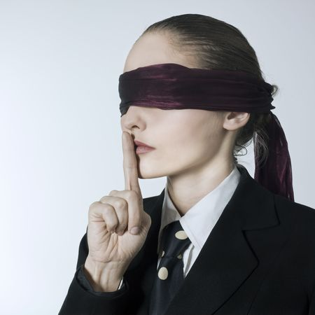 disoriented: studio shot portrait of a beautiful young blindfold woman in a costume suit