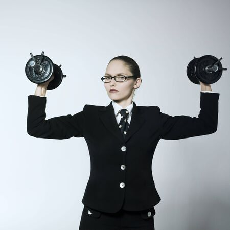 studio shot portrait of a beautiful young woman in a costume suit wearing weights Stock Photo - 2966668