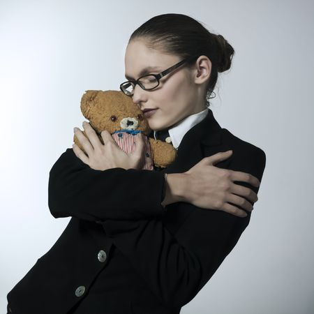 studio shot portrait of a beautiful young woman in a costume suit holding a teddy bear Stock Photo - 2966671