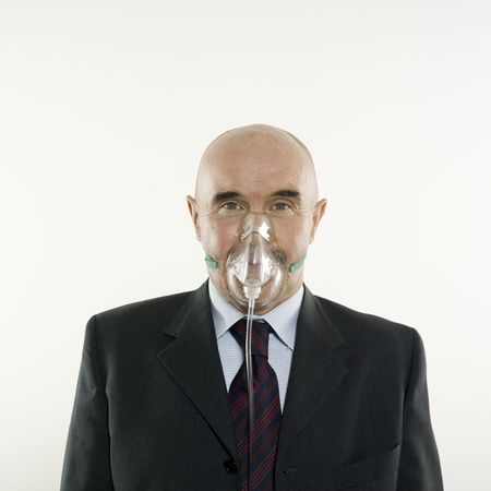 inhaling: studio portrait isolated on white background of a man senior with a oxygen mask