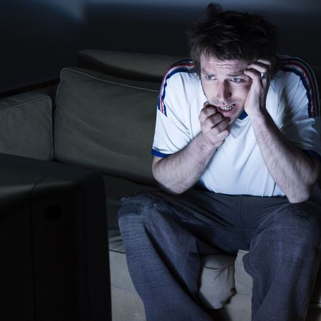pictures in a living room a funny and expressive man sitting on a couch  watching on tv  sport event Stock Photo - 2966809
