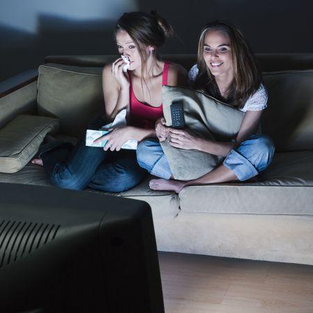 im�genes en una sala de estar de dos j�venes muchachas llorando sentado en un sof� viendo en televisi�n una pel�cula triste  Foto de archivo - 2966813