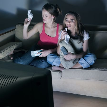 pictures in a living room of two young girls crying sitting on a couch  watching on tv  a sad movi Stock Photo - 2966814