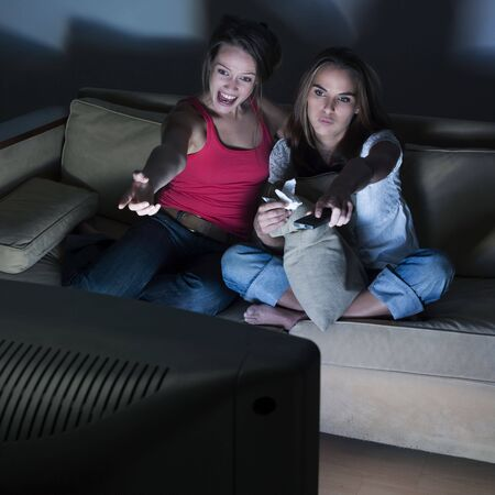 pictures in a living room of two young girls sitting on a couch  watching on tv  Stock Photo - 2966815