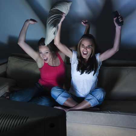 pictures in a living room of two young girls sitting on a couch  watching on tv  sport event Stock Photo - 2966816