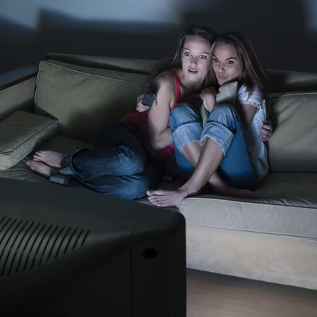 terror: pictures in a living room of two young girls sitting on a couch watching on tv a scary movie