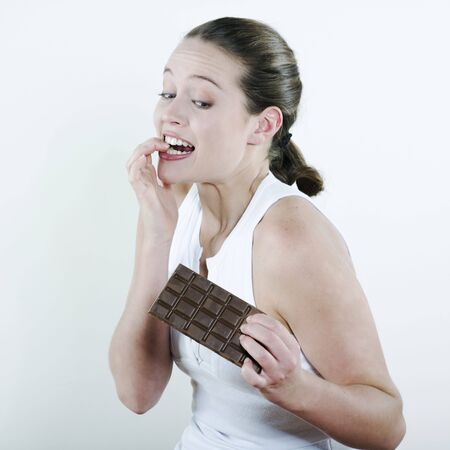 expressive mood: studio portrait on isolated background of a young beautiful caucasian woman holding a chocolate table