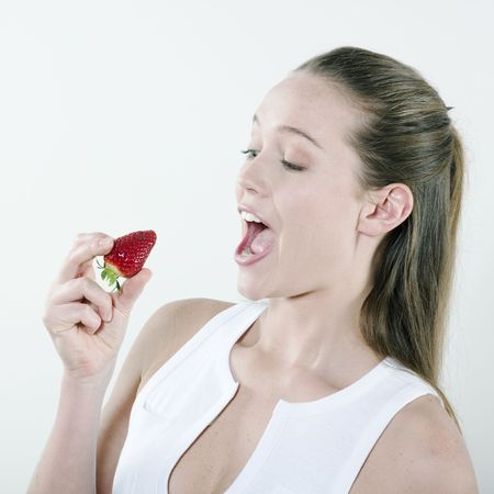 studio portrait on isolated background of a young beautiful caucasian woman eating a strawberry Stock Photo - 2966848