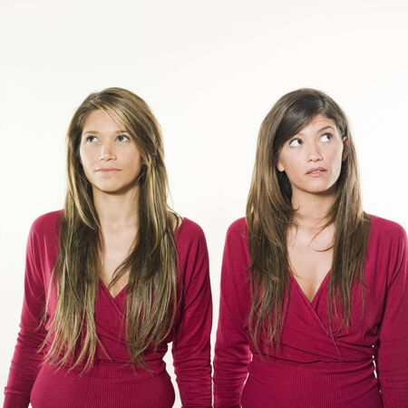 studio shot portrait on isolated background of two sisters twin women friends thinking looking up Stock Photo - 2967022