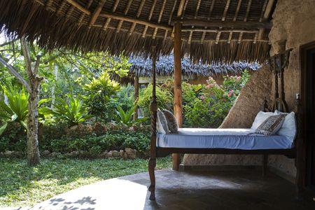 Bett im alten Stil auf einer offenen Terrasse eines Zimmers in tropischer Natur