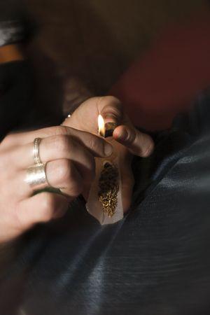 detail shot of human hands preparing a marijuana cigaret in a party