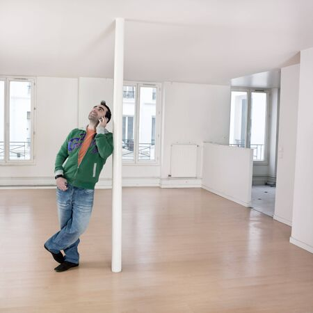 phoning: man alone inside an empty loft appartement calling by phone