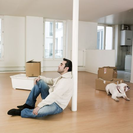 annoyance: man sitting on the floor inside an empty loft appartement with tax forms and laptop compute LANG_EVOIMAGES