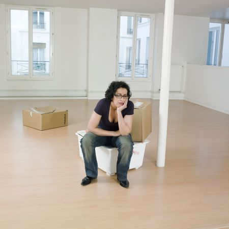 annoyance: man sitting on the floor inside an empty loft appartement with tax forms and laptop computer LANG_EVOIMAGES
