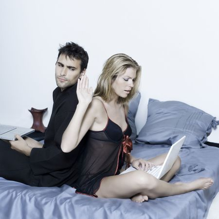 seduction: beautiful young caucasian couple in a bed on isolated background with computer laptop